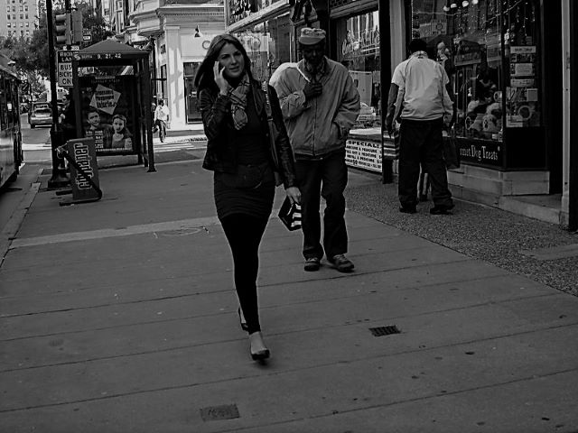Black and white photograph of a girl being noticed as she walks down the street. Harassment in Public