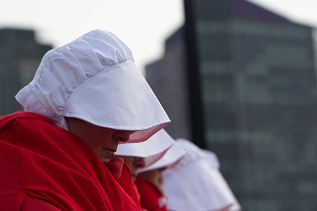 "Photo of ""A Handmaid's Tale"" costume white hat red cape. environment climate change"