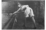 Black and white photograph of a prostitute in lingerie playing pool.