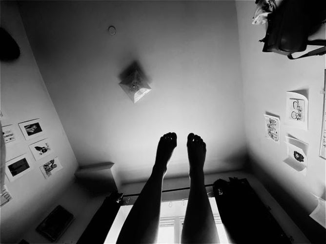 Black and white photograph of feet in the air. from: PWCD - Covid-19 messages.